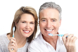 An older man and woman holding toothbrushes