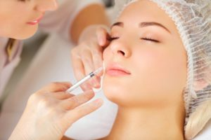 woman receiving cosmetic injection in her face