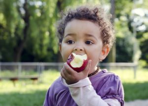 a child eating an apple while playing outside