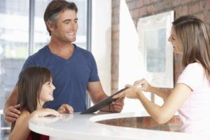 Father and dentist discuss children's dental insurance coverage